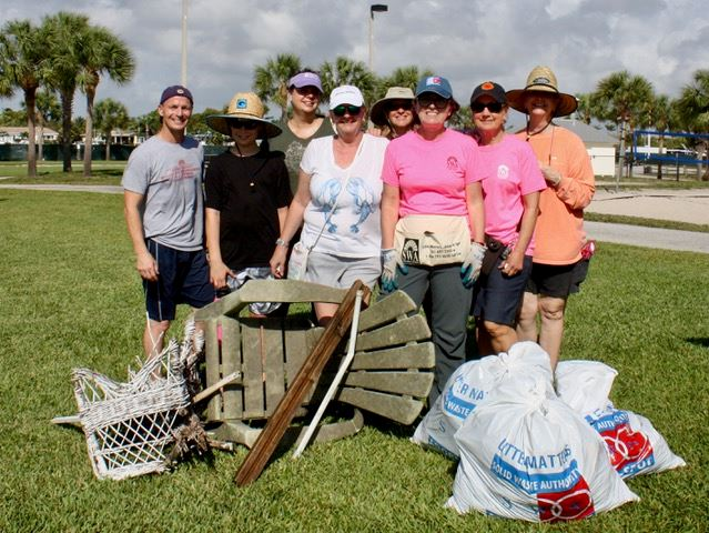 Group of eight volunteers standing in Anchorage Park next to a pile of trash they collected from the