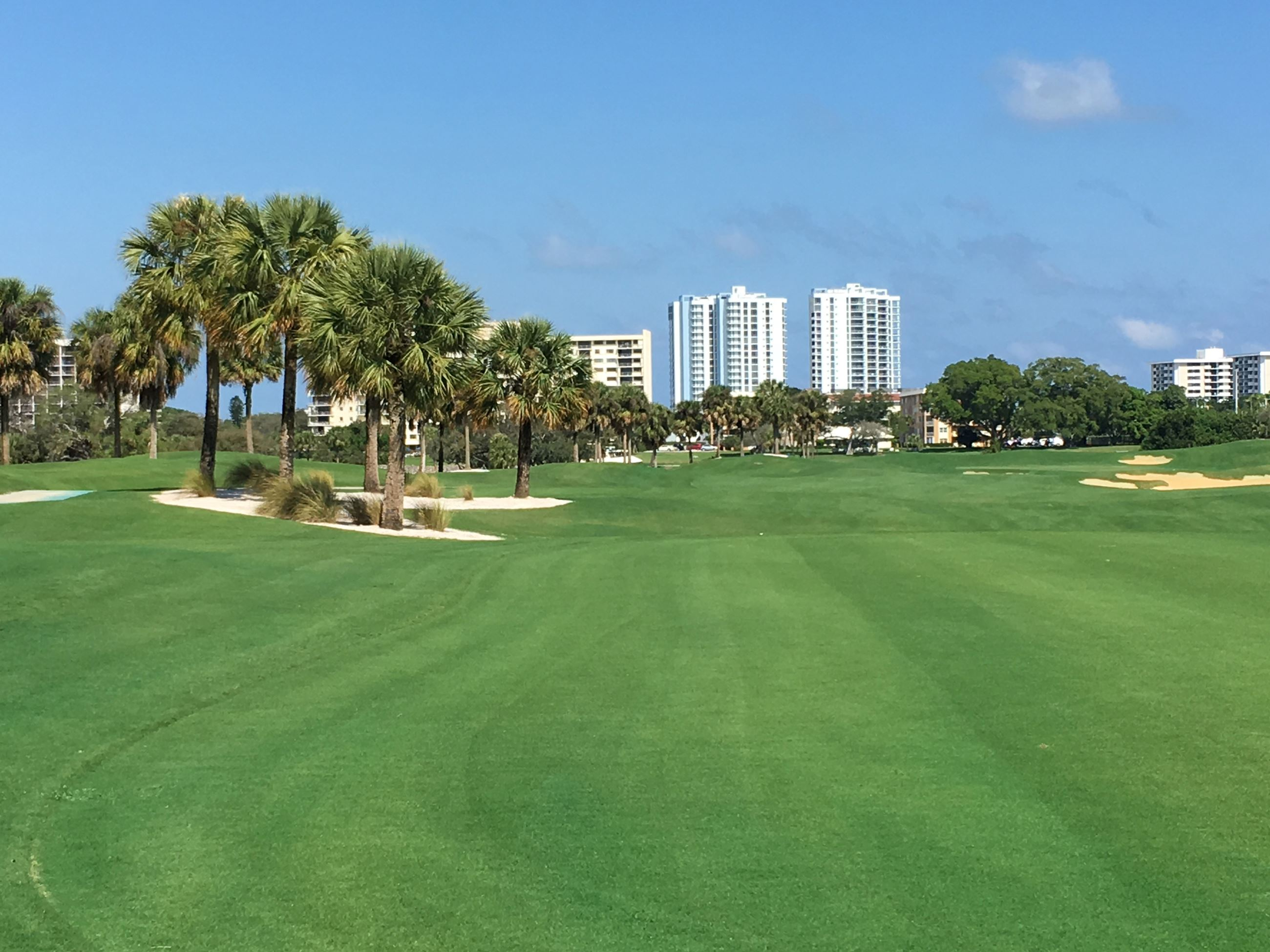 Image of green turf at first hole with high rise condominiums in the distant background