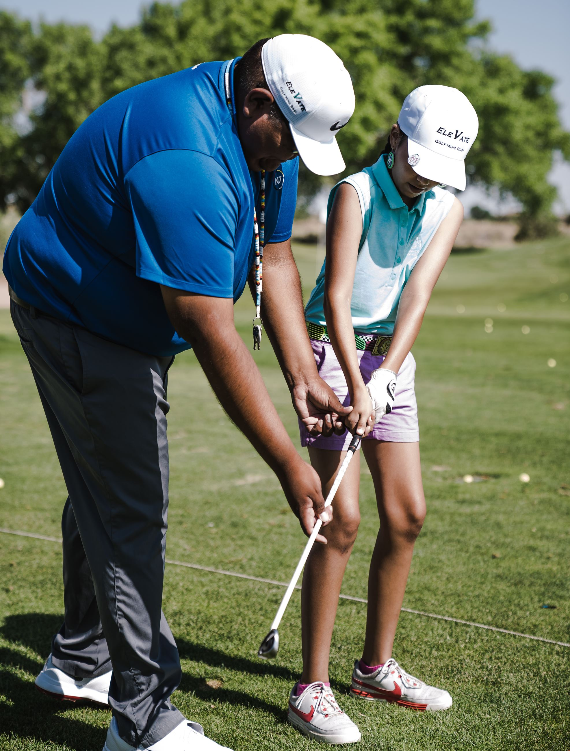 Golf coach teaching child how to swing a golf club