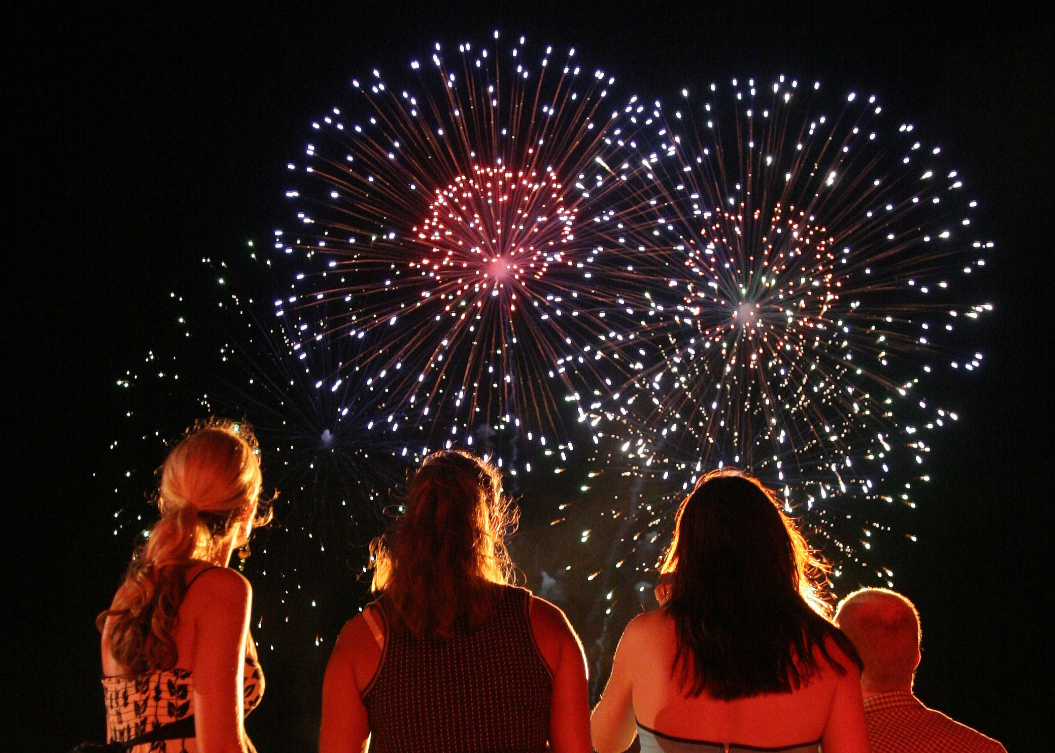 Silhouettes from behind of a group of women looking up at exploding fireworks in the dark sky