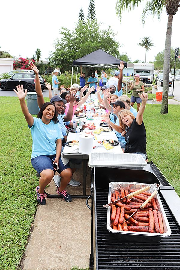 NET volunteers sitting at a picnic table on a residential sidewalk, having lunch and waiving at came