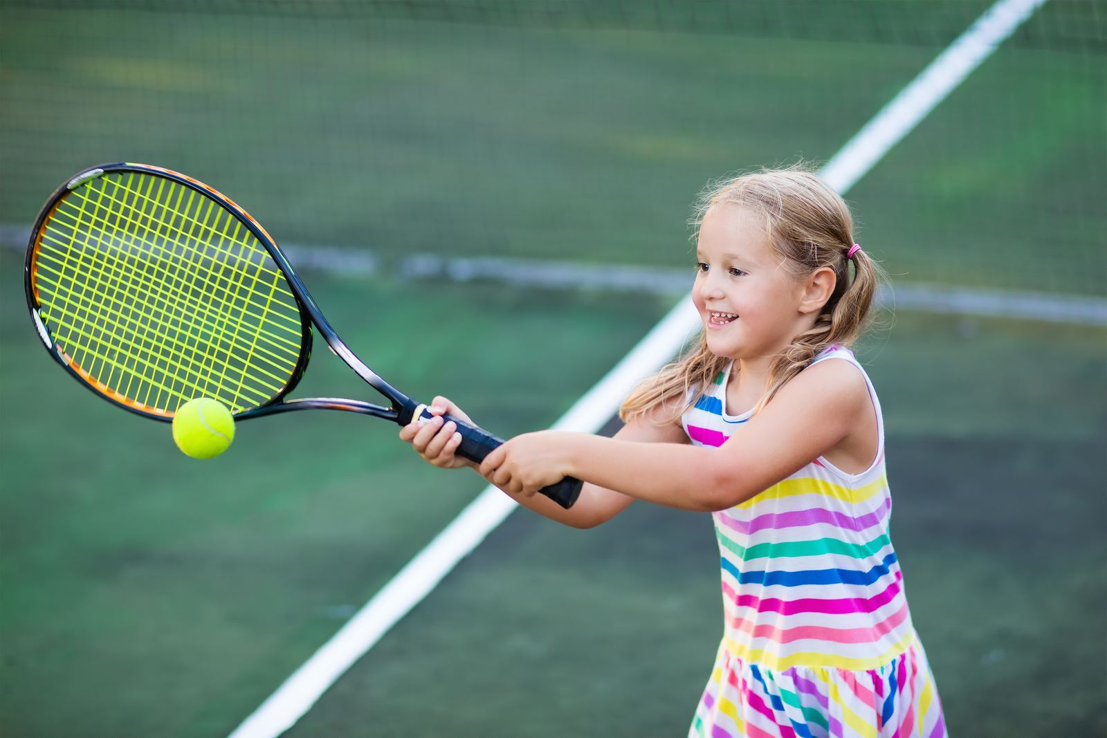 Girl, about 8 years old, swinging tennis racket