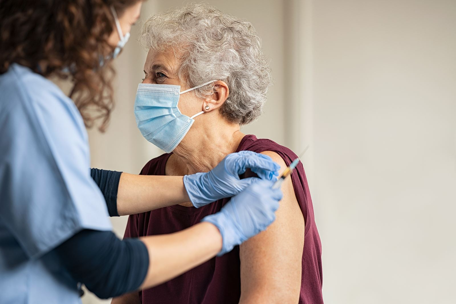 Woman getting vaccine from healthcare worker