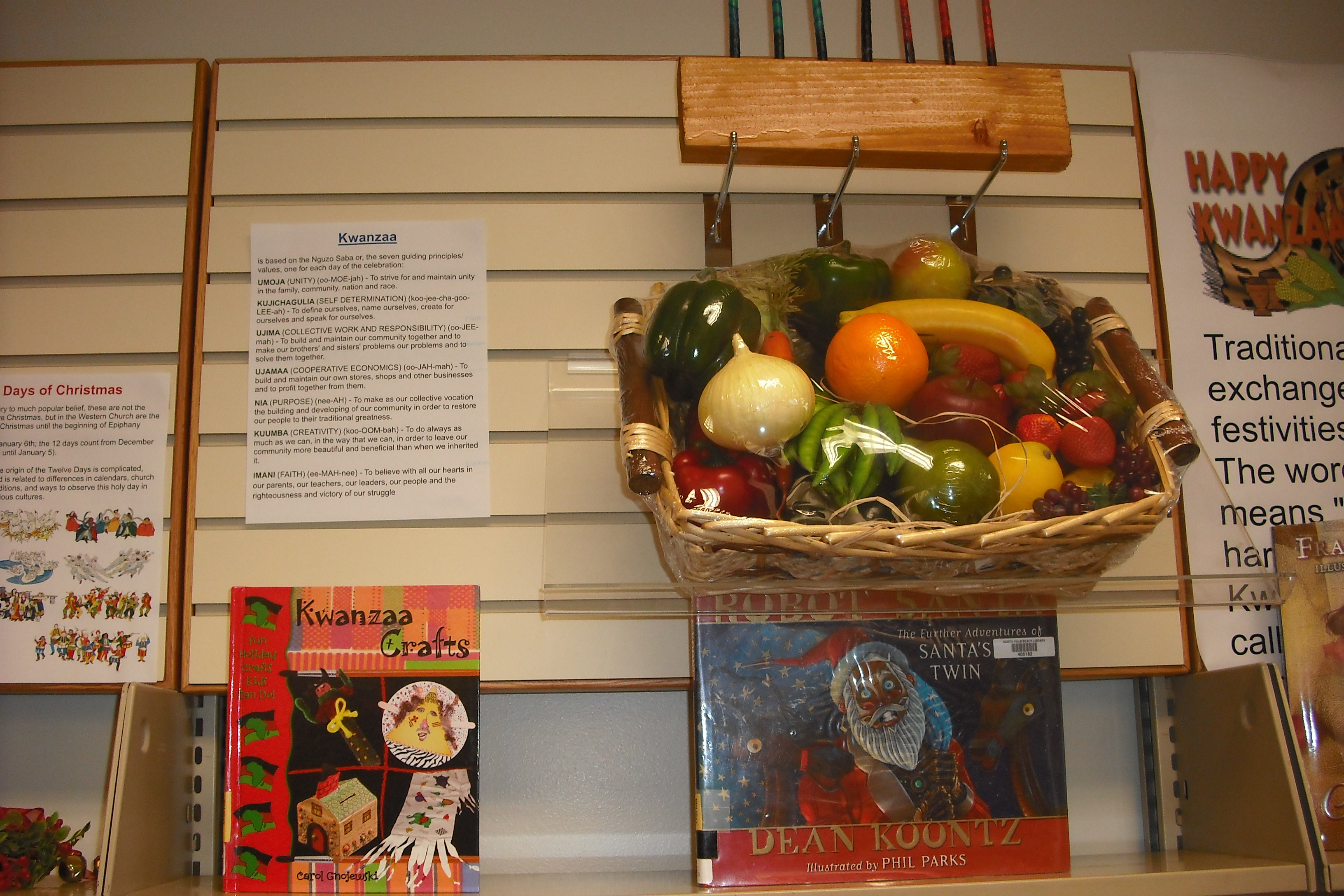 A fruit basket sits next to a paper with information about Kwanzaa