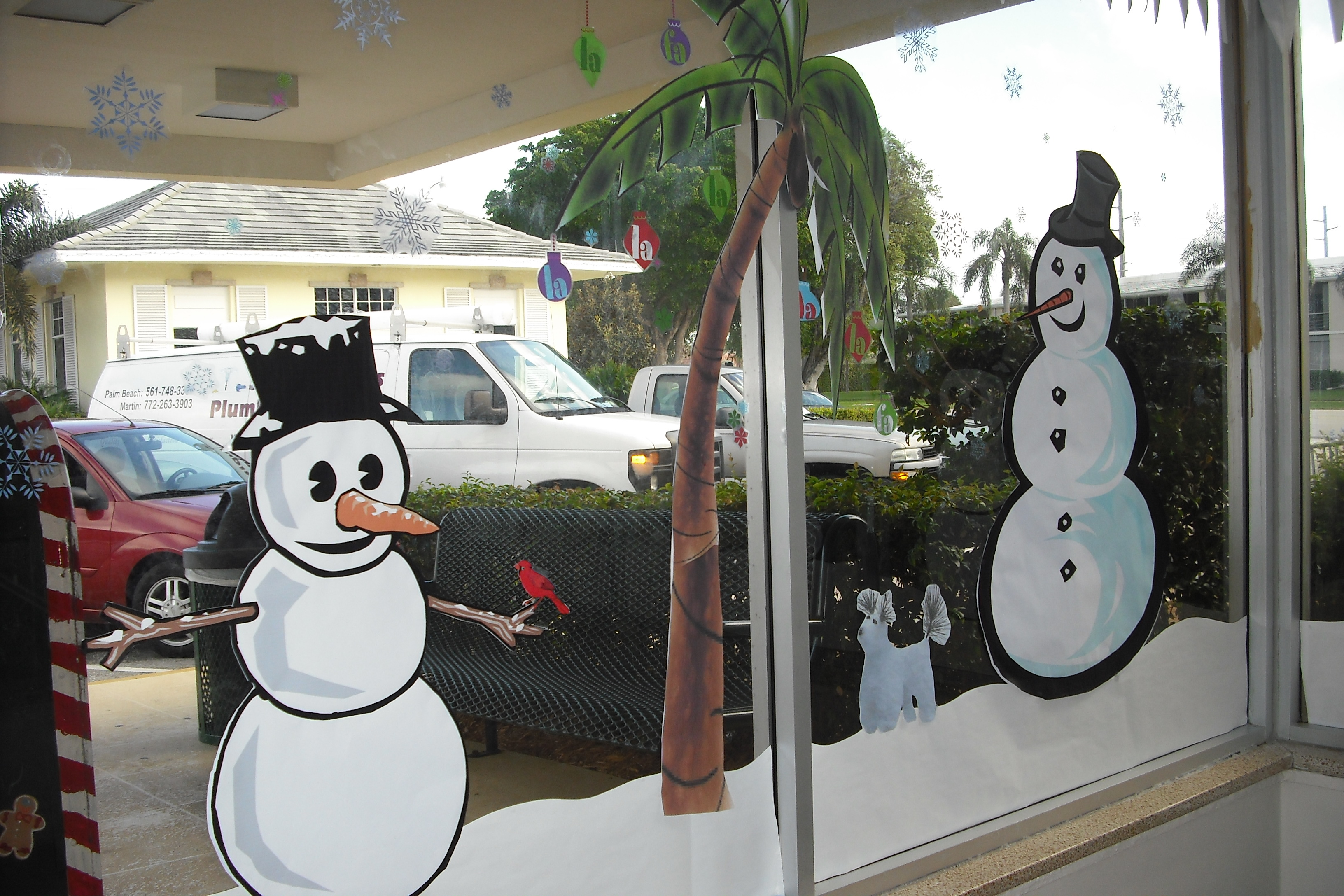 A palm tree decoration in the window with Christmas ornaments