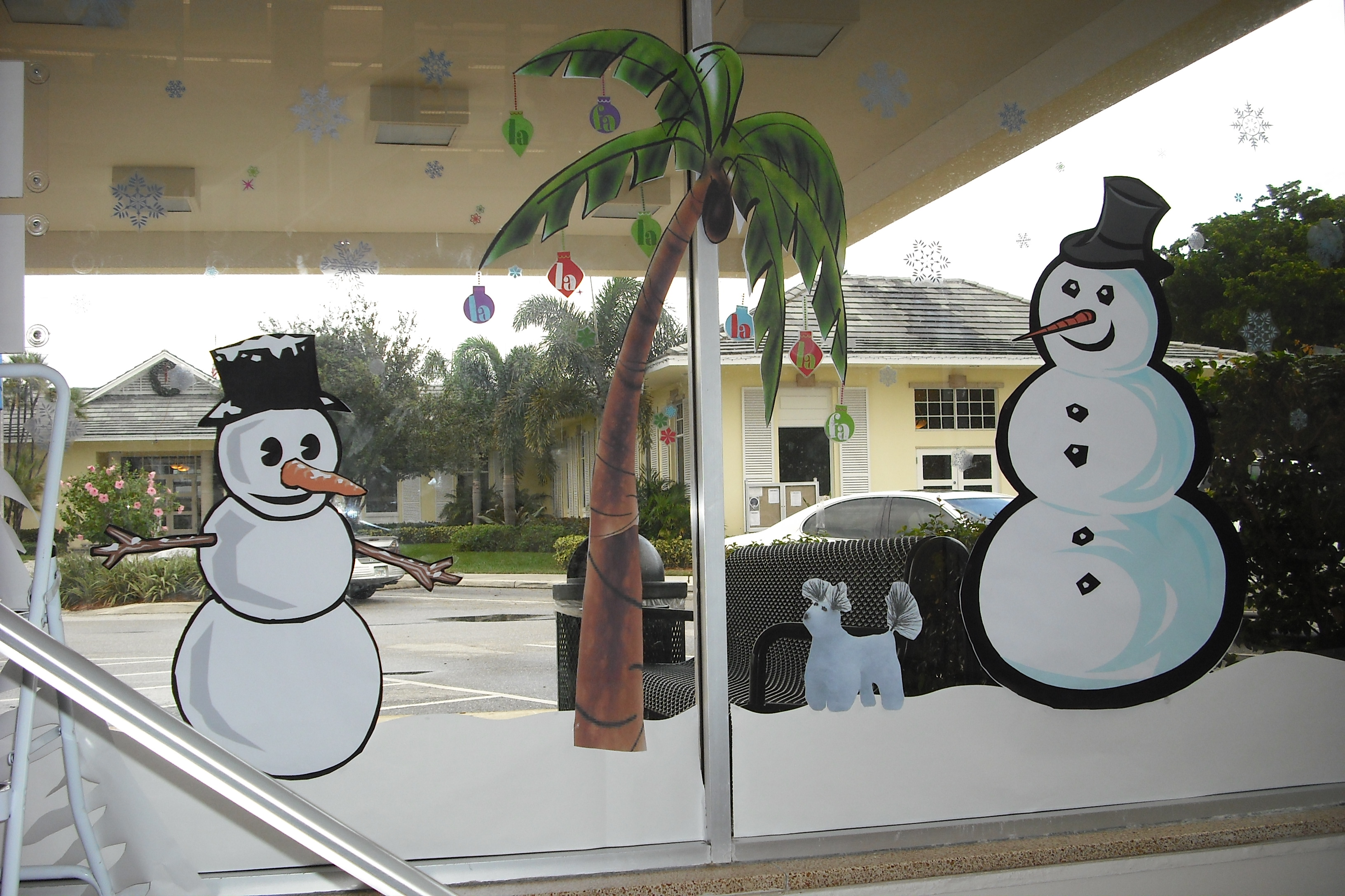 Snowmen gather around a festive palm tree