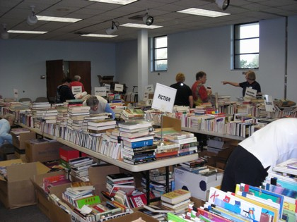 Multiple tables full on all kinds of books with volunteers working to organize them