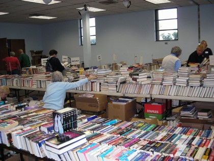 Women in a blue sweater moving books around on the table