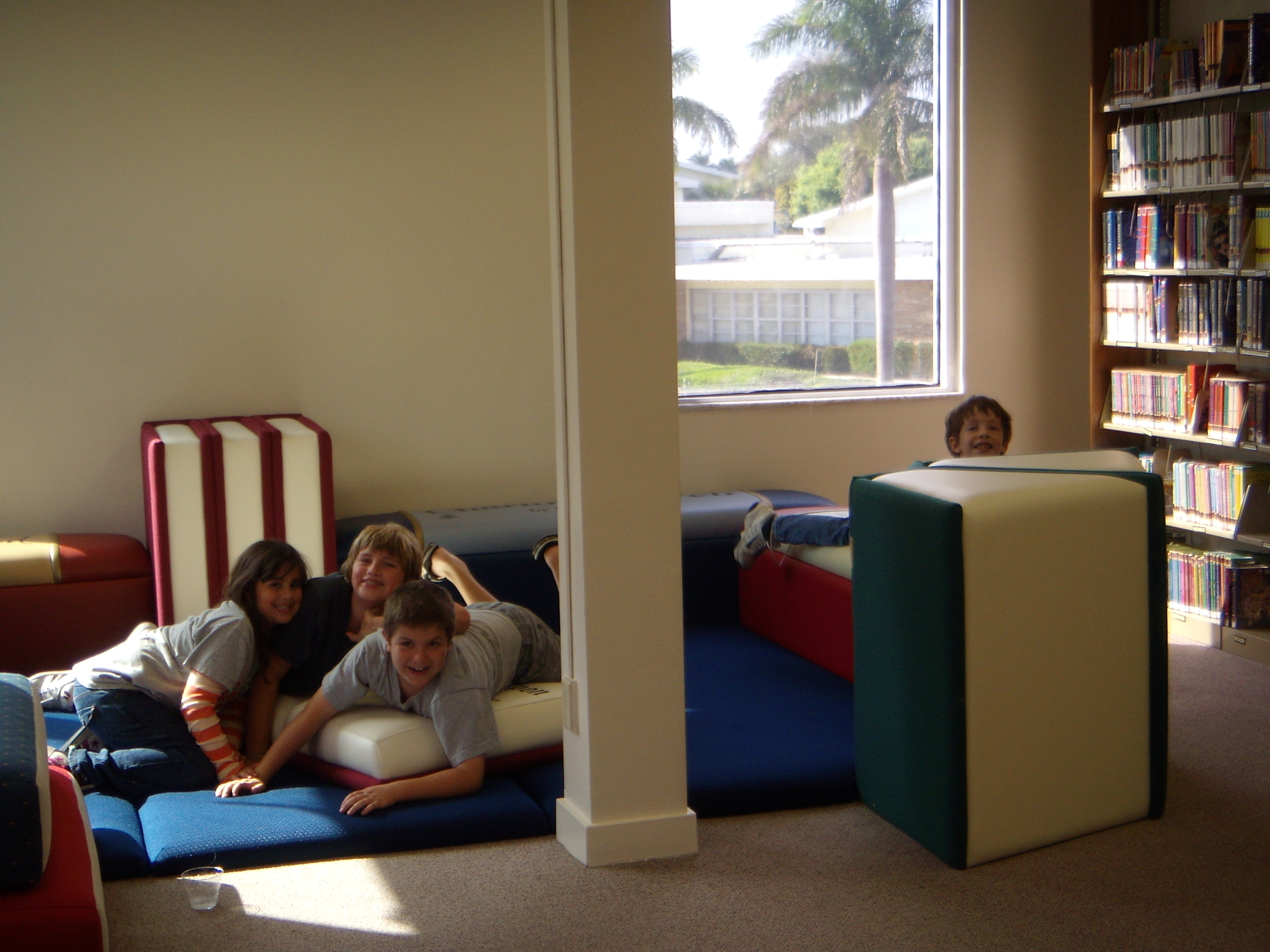 Children laying on book mat and book furniture