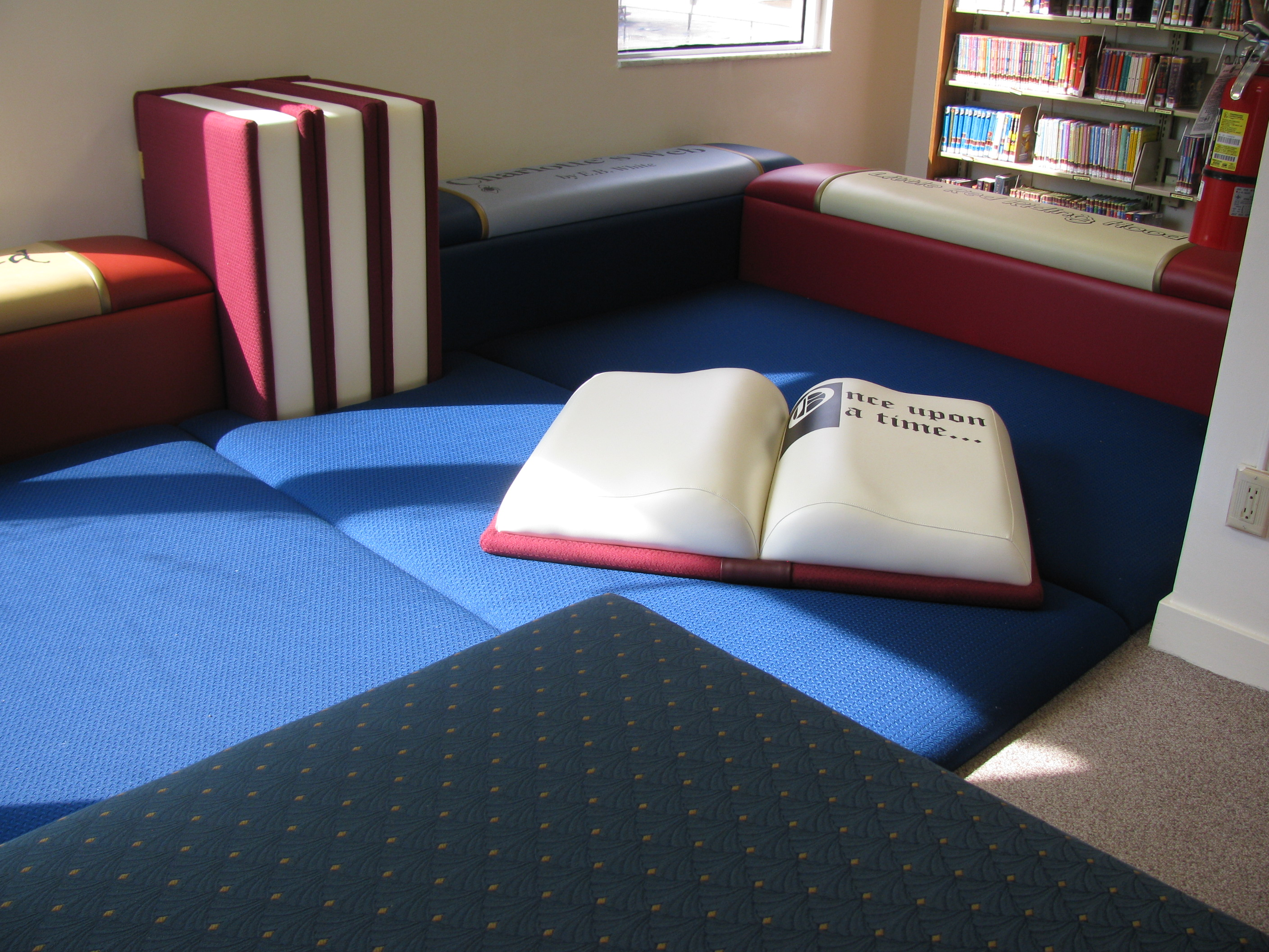 Blue mat on floor with open book pillow