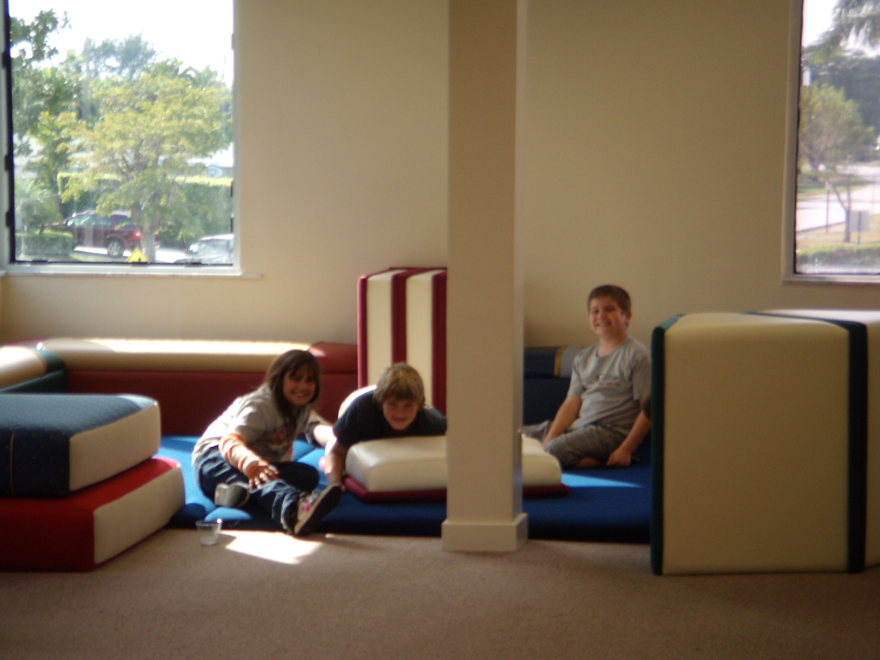 Children laying on book furniture
