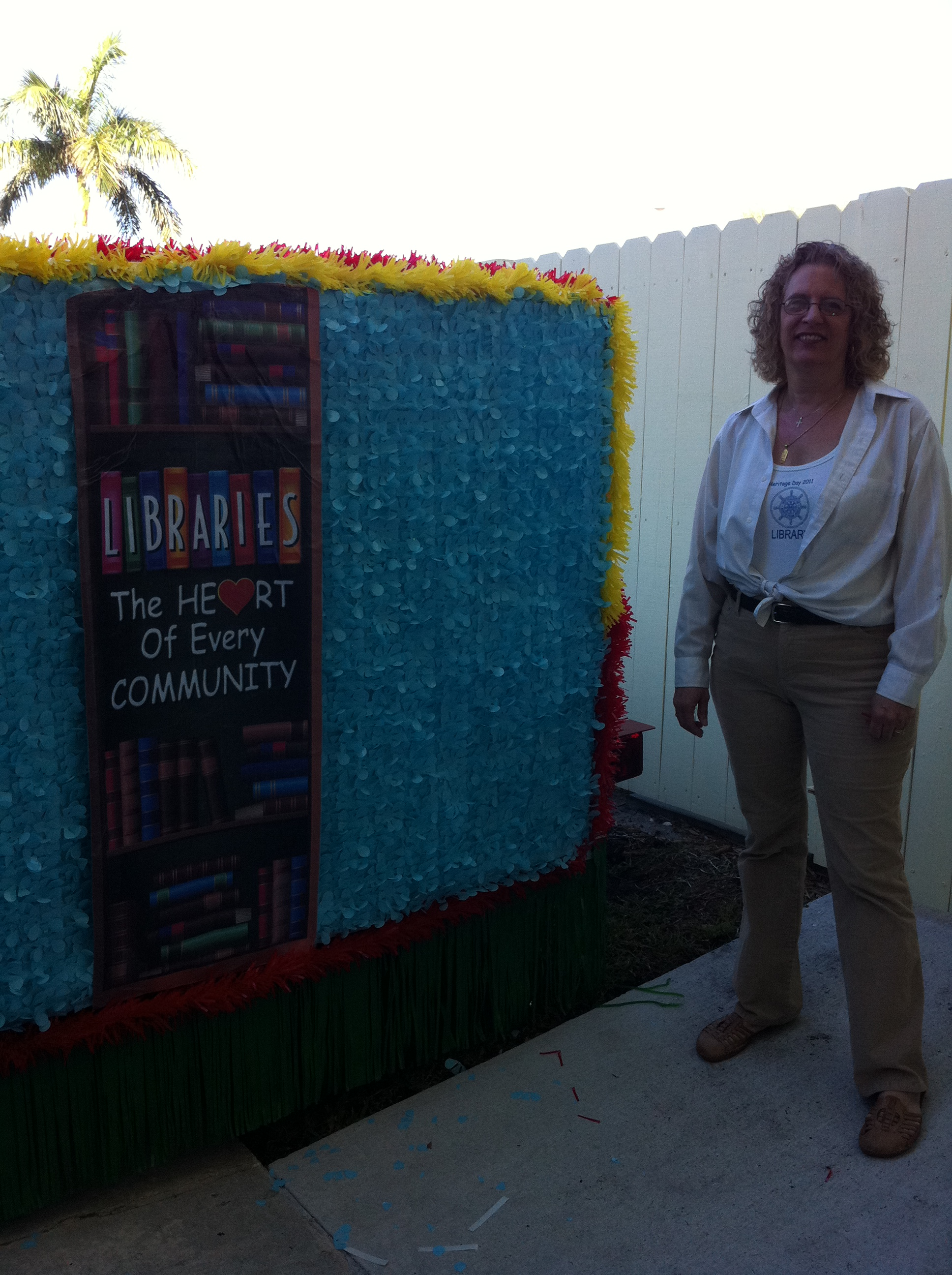 A participant stands next to the Library's Float