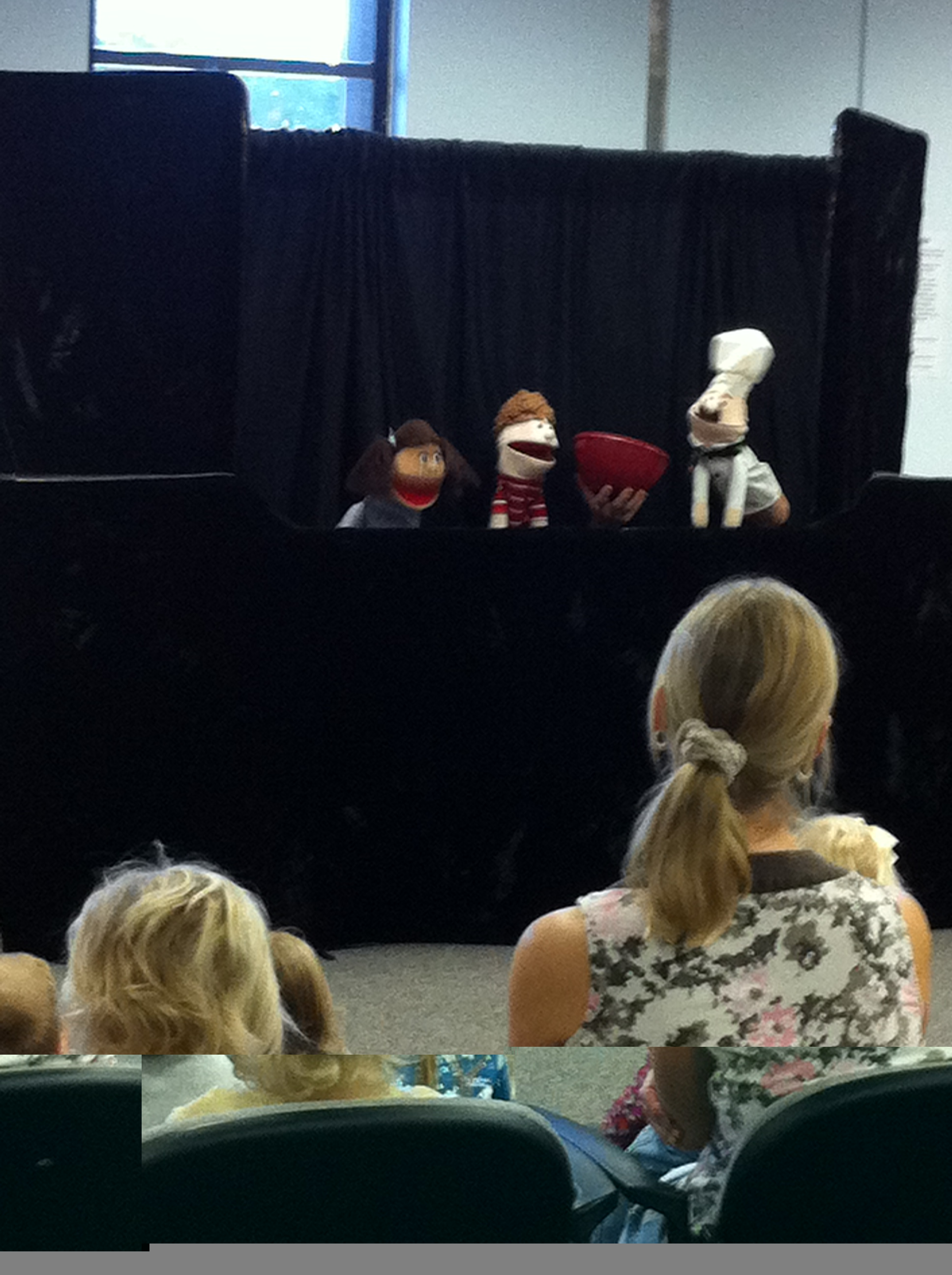 A puppet dressed as a chef presents a bowl to the other puppets