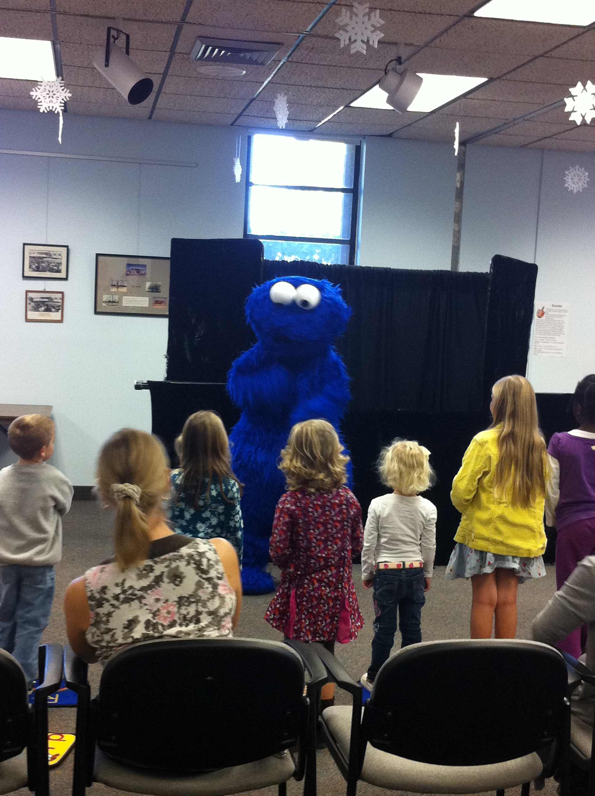 A large, fuzzy creature talks to the children at the event