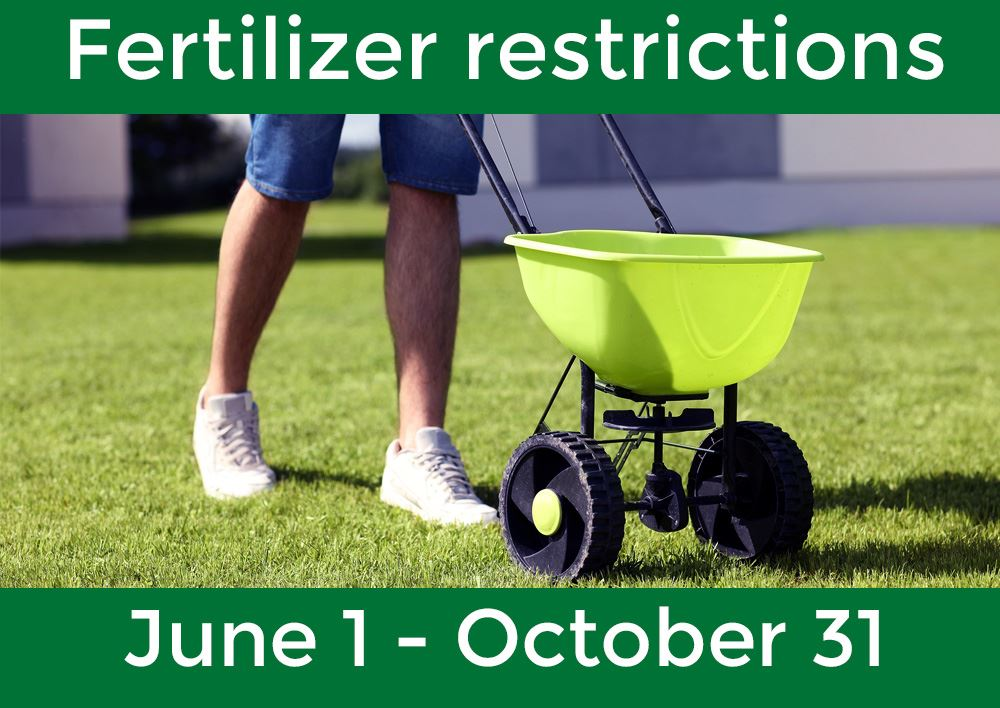 Image of man's legs pushing fertilizer spreader on green grass, with text saying fertilizer restr