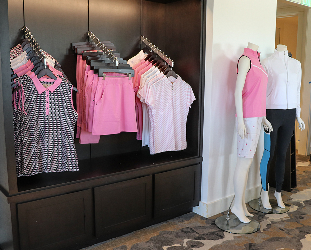 Golf clothes on rack at pro shop in clubhouse.