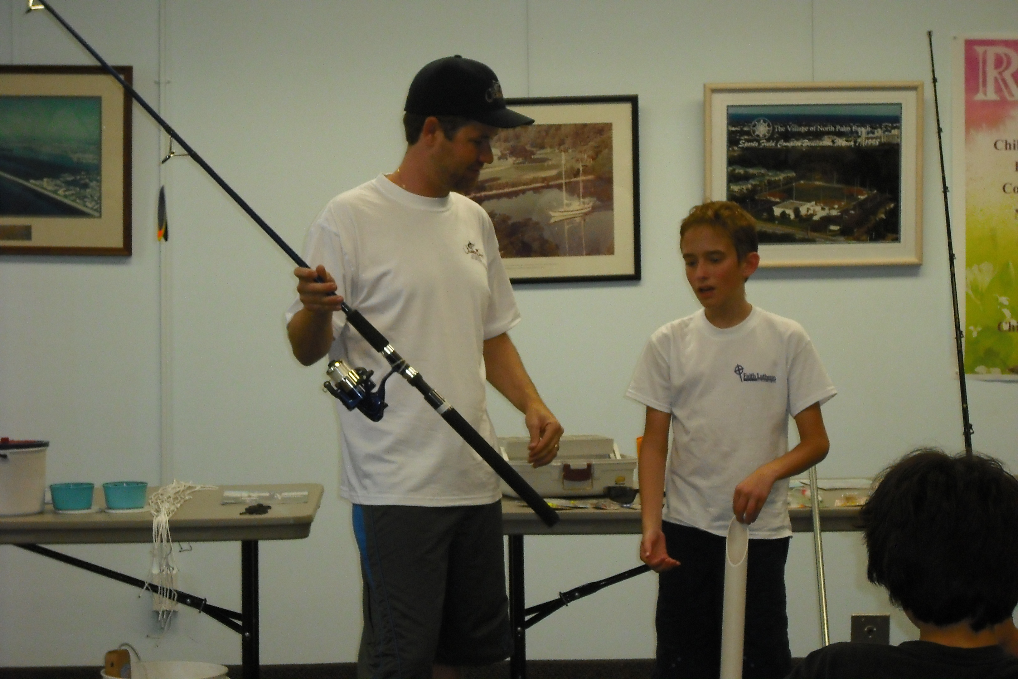 A boy is brought up to look at another fishing pole