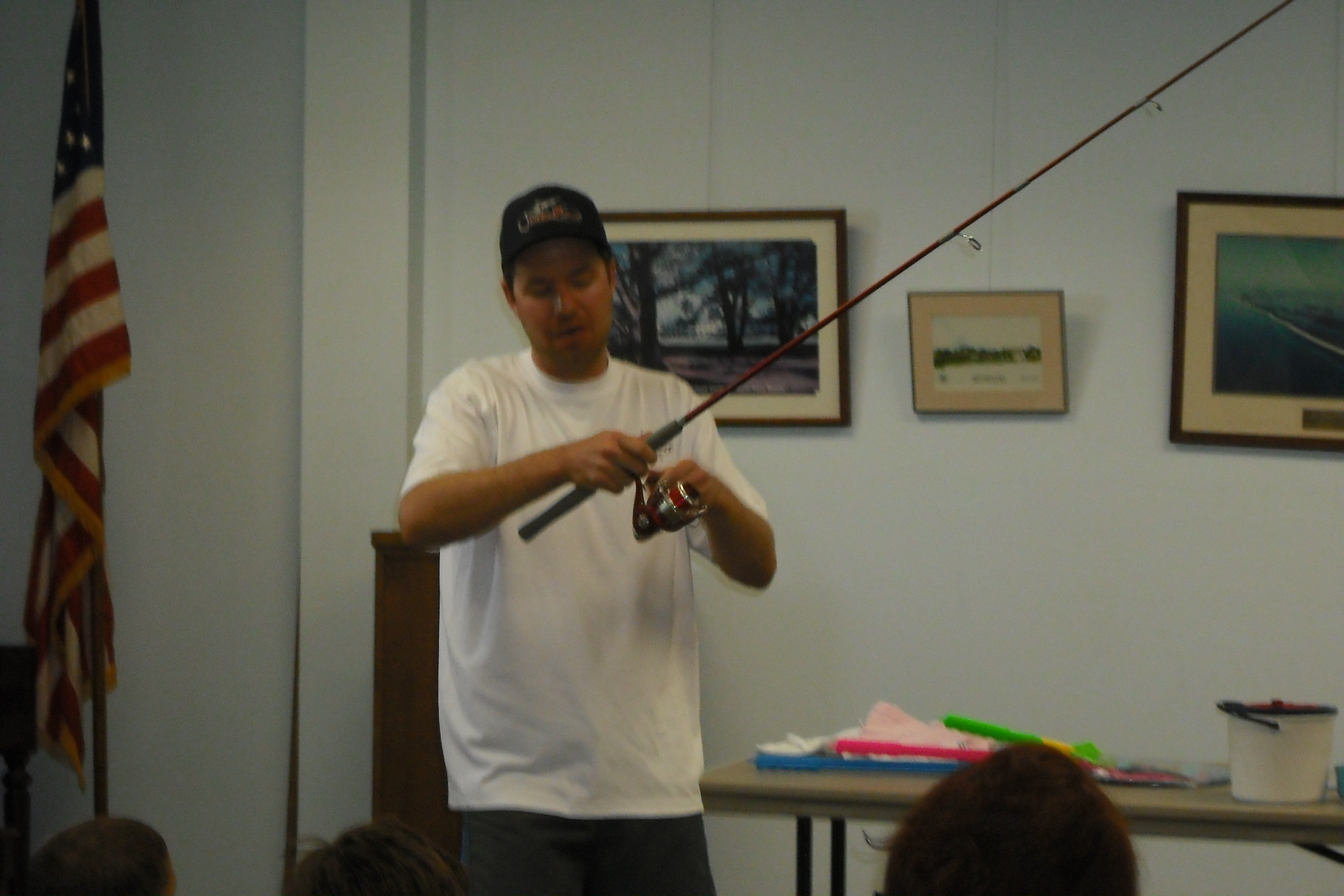 The speaker shows a fishing pole to the audience