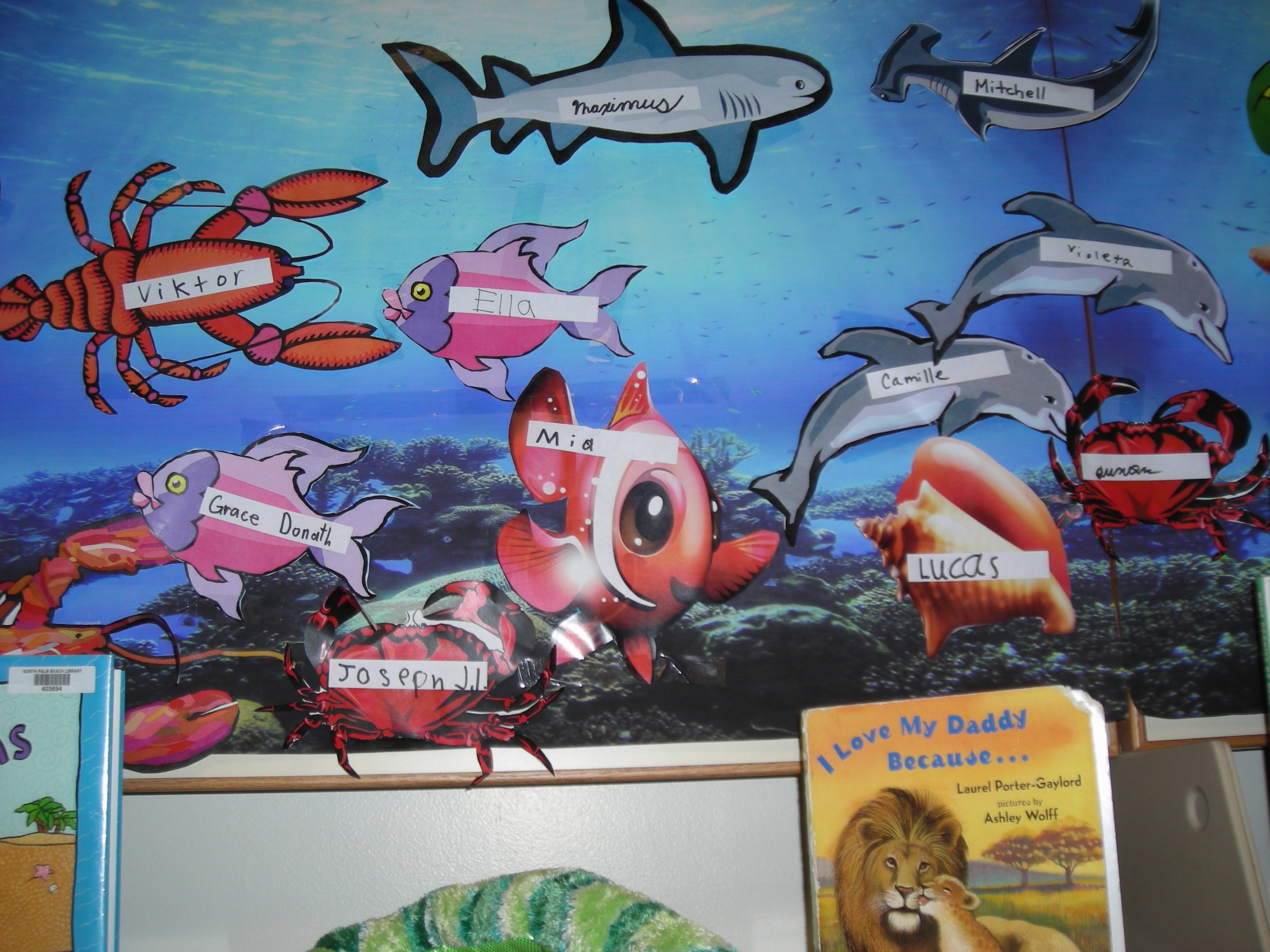 Children have written their names on the fish decorating the wall